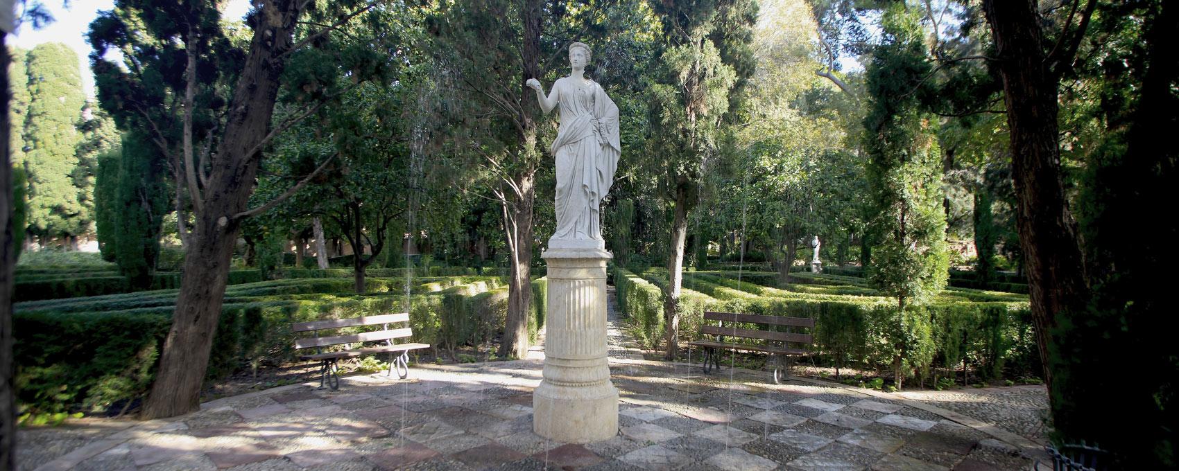 La estatua de la diosa Flora se ubica en el centro del Patio de los Surtidores desde donde se levanta sobre su pedestal y domina el espacio del parterre nuevo.