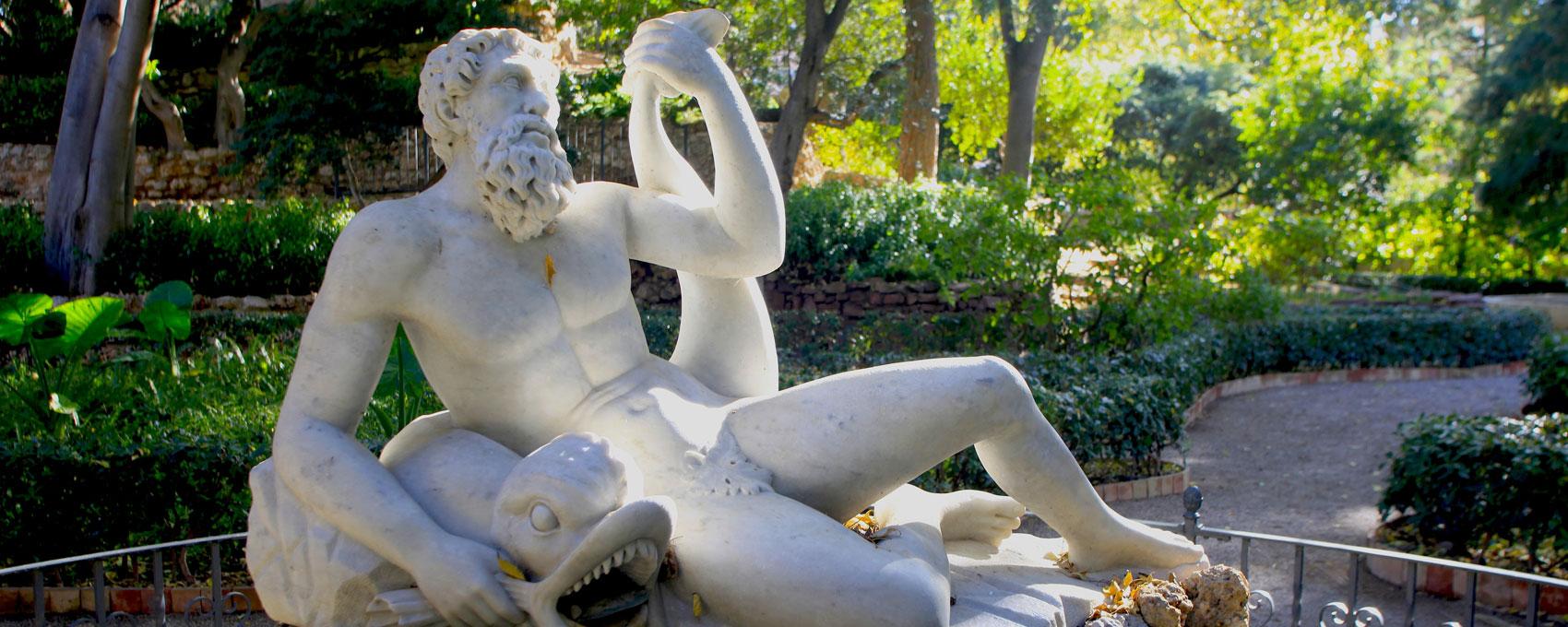 """La fuente que representa al dios Poseidón o Neptuno está situada al pie de la """"Montañita"""" y junto a la entrada de la Gruta. La figura de mármol descansa sobre un pedestal realizado con guijarros."""