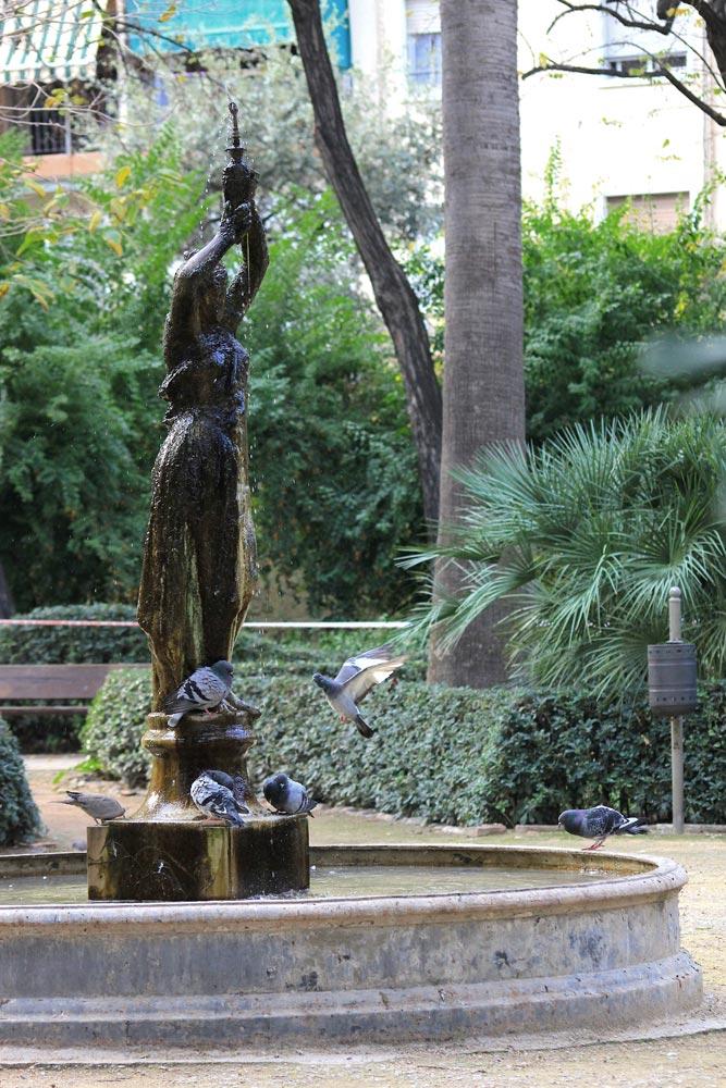 Ubicada en el centro del jardín destaca esta fuente en cuyo centro una figura femenina realizada en hierro colado alza sus brazos en alto sobre un pequeño pedestal de mármol blanco.